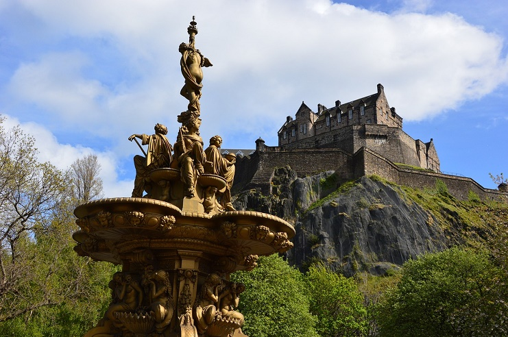 A view of Edinburgh Castle from below in the park with a spectacular fountain in front