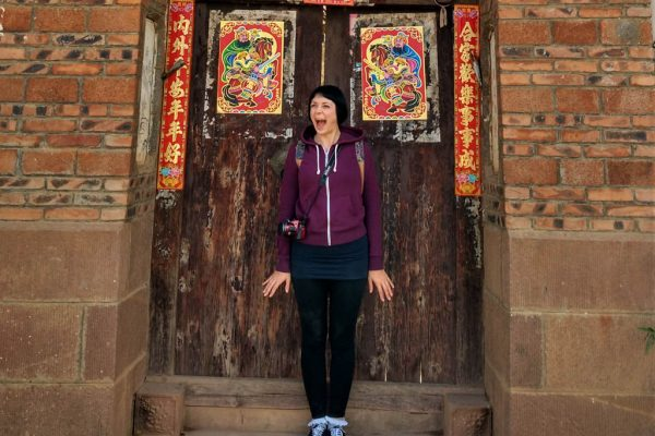 Blogger Alice standing in front of a chinese door in China