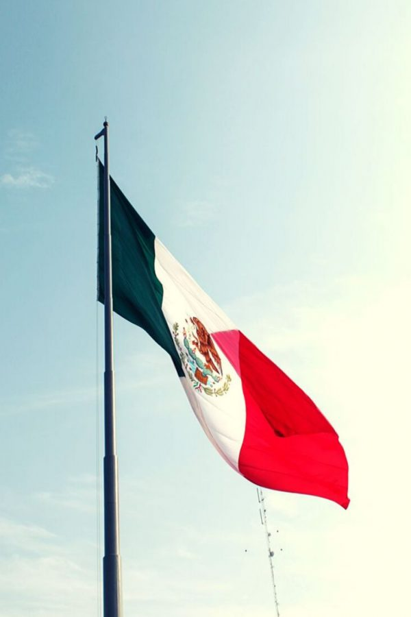 Flag of Mexico flapping in clear blue skies. Mexico City is a great female solo travel destination for 2020