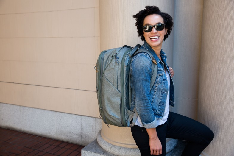 Woman carrying a teal green Peak Design 45L Travel Backpack