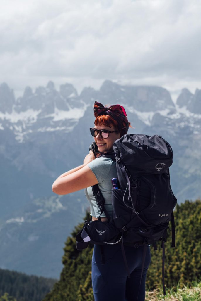 Alice Teacake looking out to the Dolomites with a blue Osprey Kyte 36 Backpack on her back