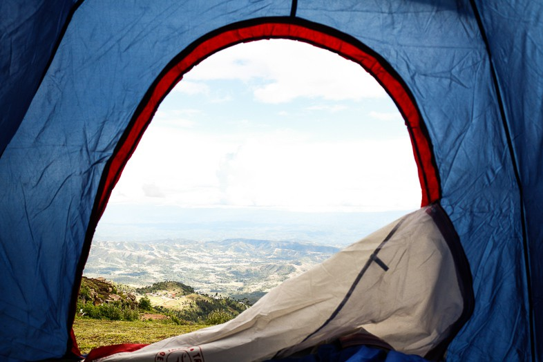Scene from the inside of a blue tent looking out onto rolling hills and blue skies