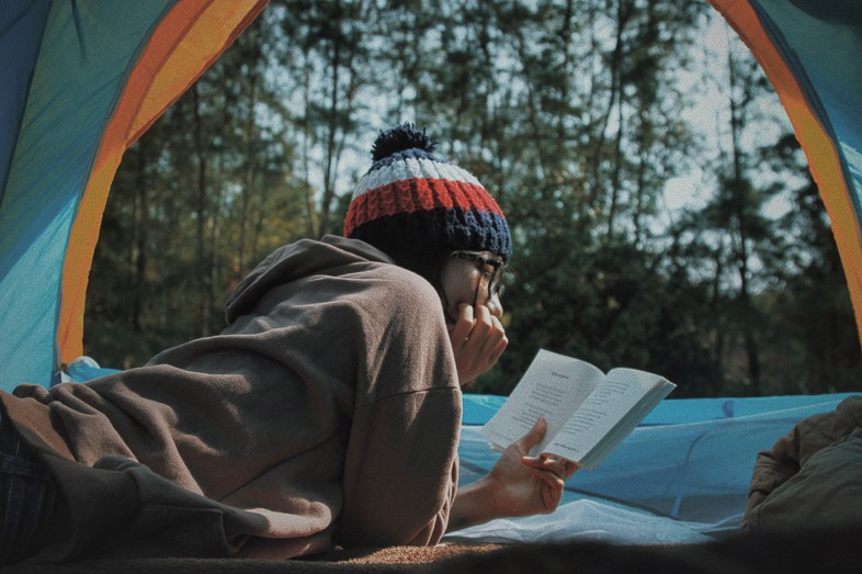 Woman reading a book in her tent in the woods camping alone