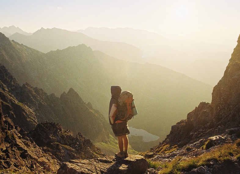 Solo female traveler with a backpack looking out onto a scenery of mountain tops