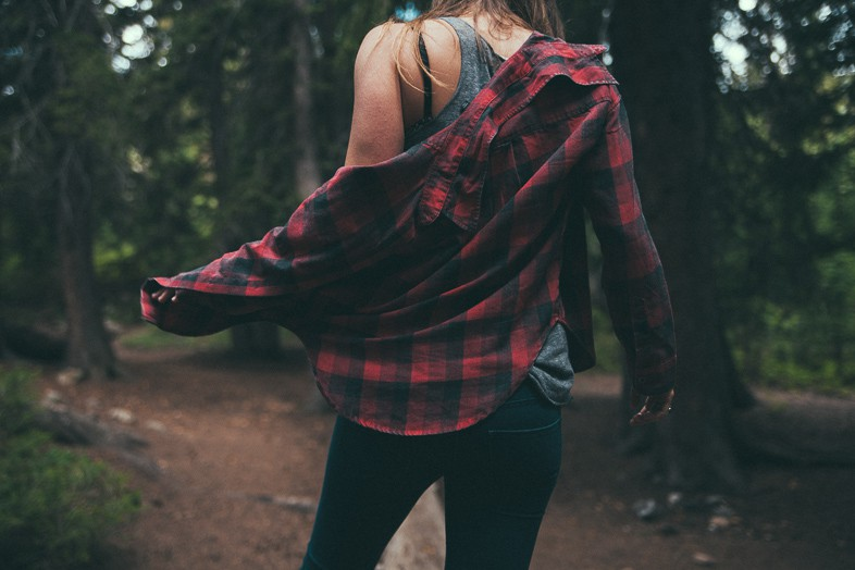 Woman running wearing a red and black chequered shirt in the wilderness