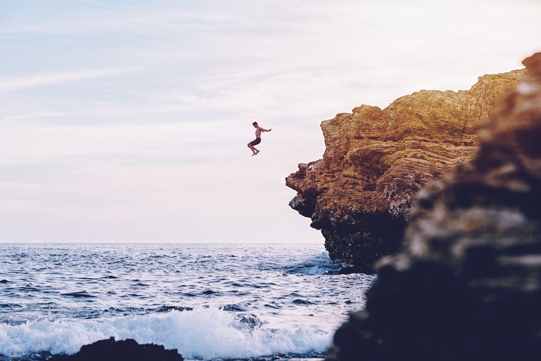 Adventurer jumping from a cliff into the sea