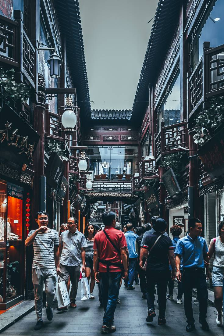 Crowd of Chinese people walking through Yu Gardens in Shanghai China in the narrow alleyways