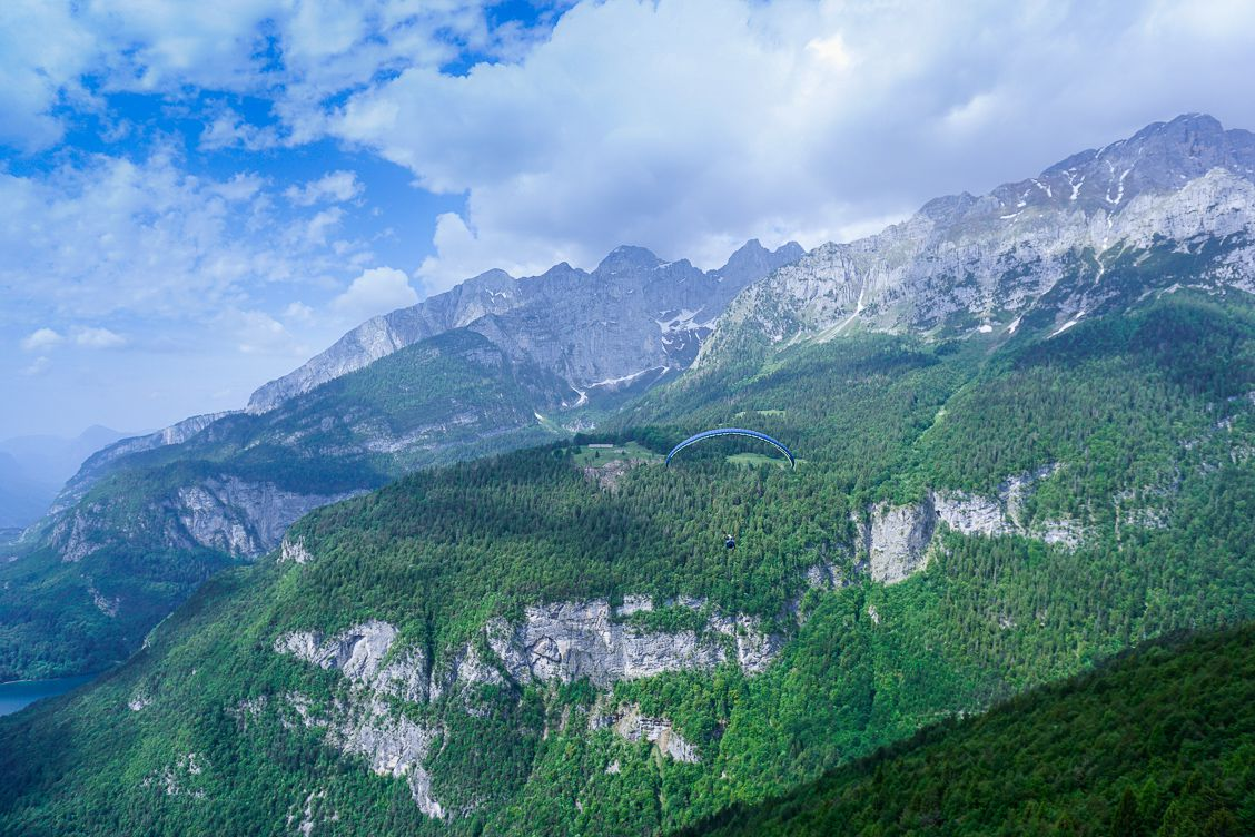 Glorious views of a paraglider flying above Lake Molveno with the Brenta Dolomites behind them