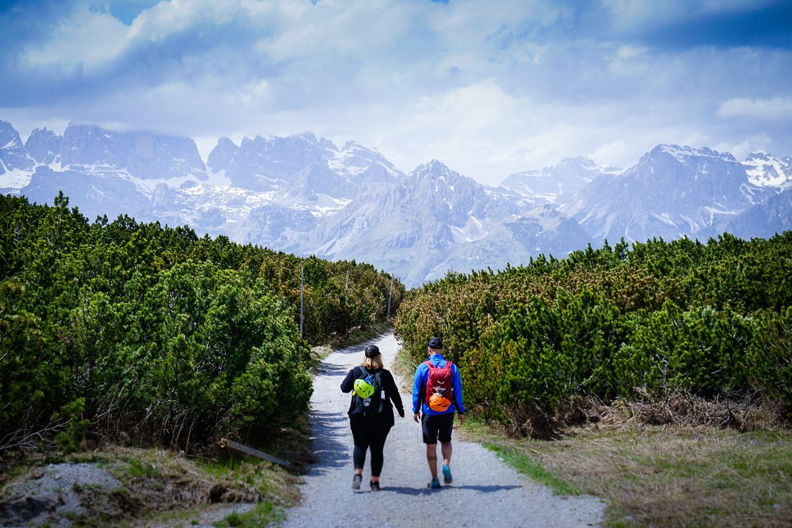 Man and woman hiking along a path on Paganella Mountain in Trentino Italy
