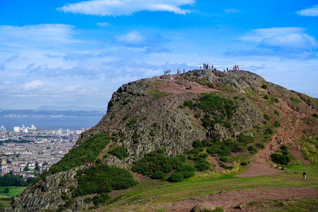 Hikers on Arthur's Seat looking down upon the Edinburgh Festival in Scotland