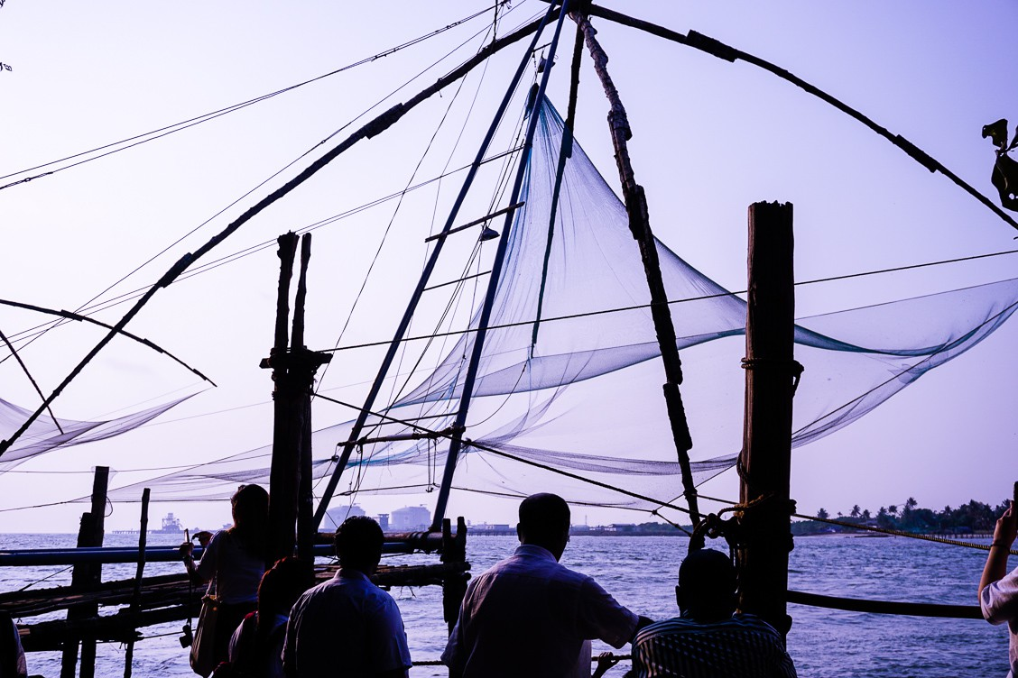 Fishers surrounding their set-up Chinese fishing nets. The nets are strung along a frame created by four posts that are connected at the top in a tent shape.