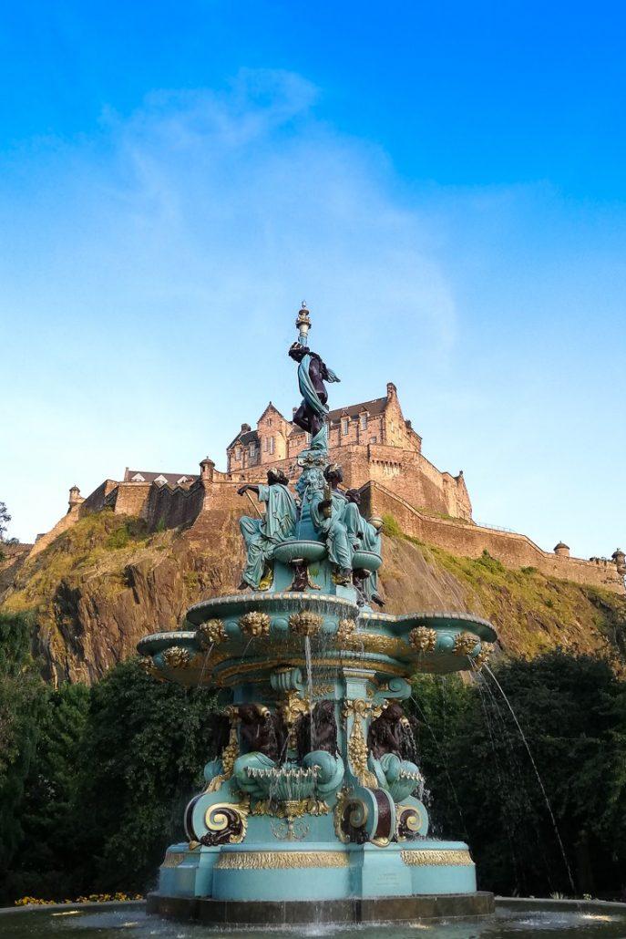 View of Edinburgh Castle in front of Ross Fountain in Princes Street Gardens