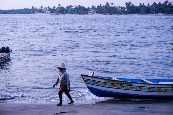 Fisherman in Kochi walking next to his boat on the shore.