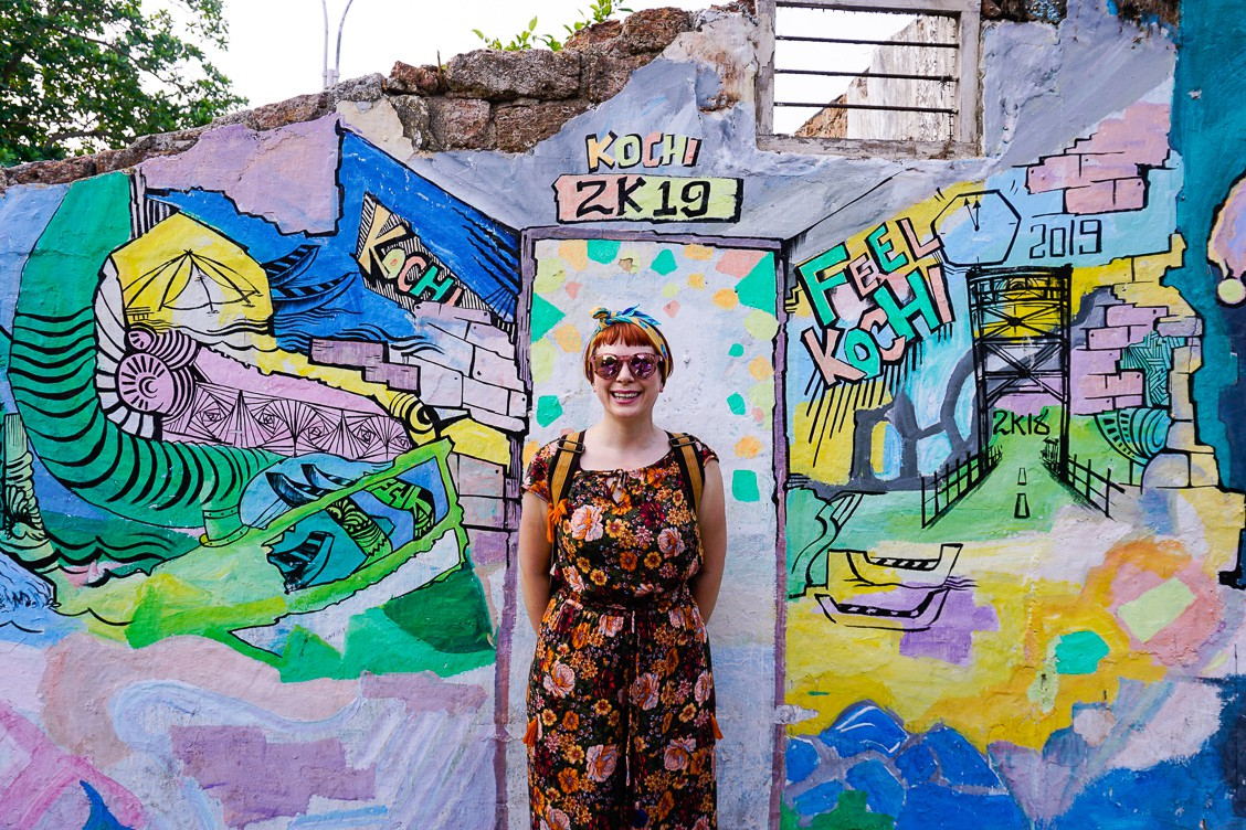 Alice smiling and standing against a ruined building in Fort Kochi covered in blue, yellow and green graffiti.