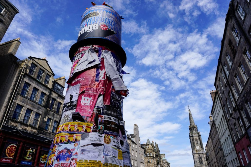 A pillar covered in Fringe posters advertising different shows