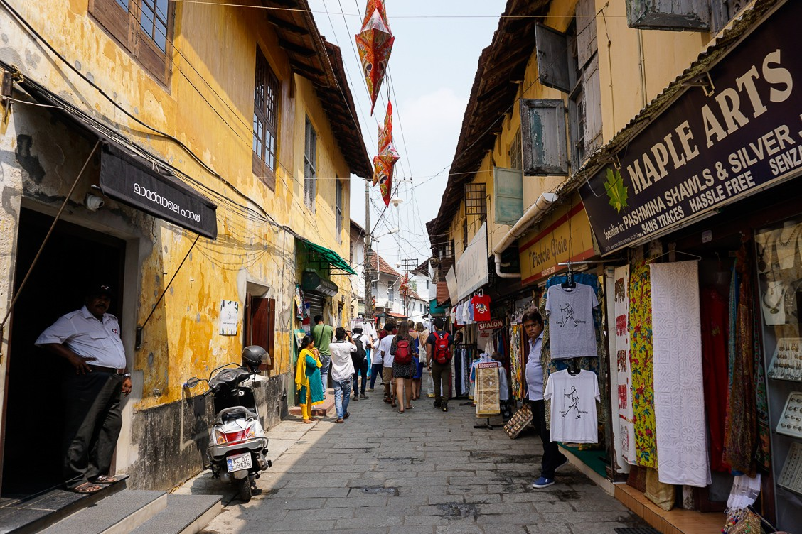 A busy, narrow street with shopkeepers on each side standing outside their shops. They sell pashminas and other clothing items.