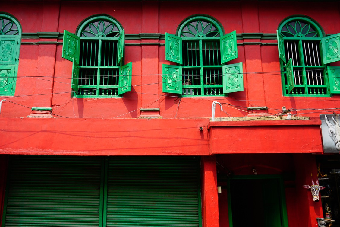 Red building with green windows and shutters as well as a matching green door.