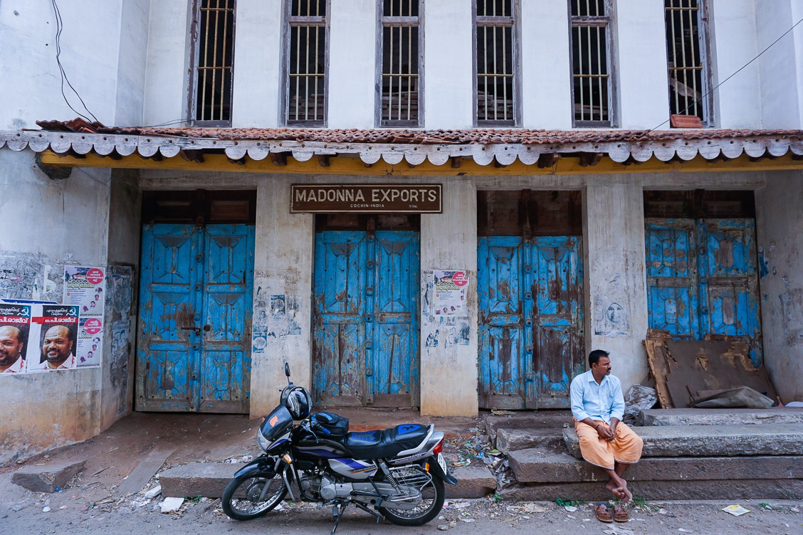 "An old, white building featuring four blue double doors and a sign that says ""MADONNA EXPORTS"". There is also a motorcycle in the middle of the frame with a man resting to the right of it."