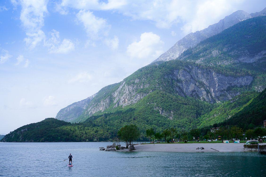Man paddle boarding upon Lake Molveno against the epic backdrop of the Brenta Dolomites