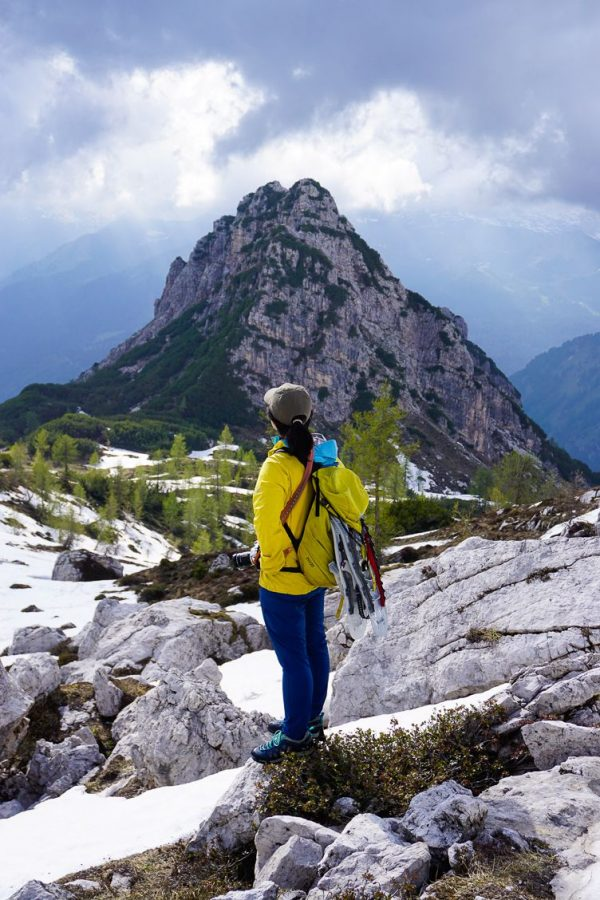 Girl in yellow coat looking out upon the Dolomiti di Brenta