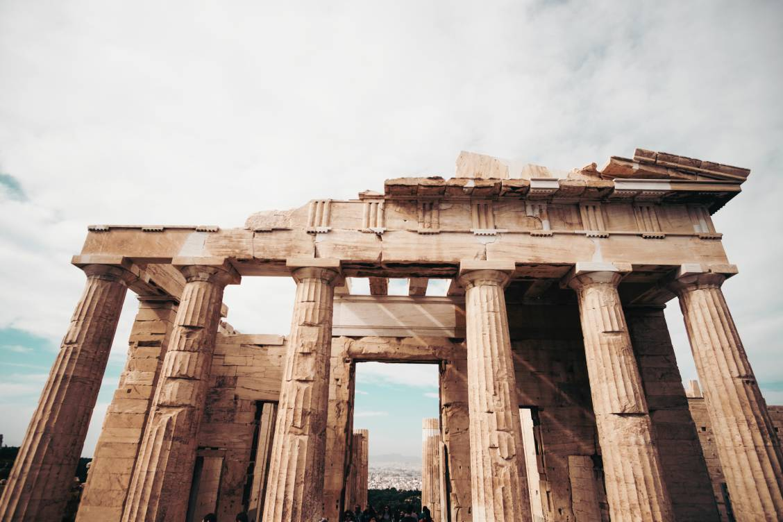 Photo of the ancient Acropolis of Athens featuring the ruins of 6 Doric columns in the forefront.