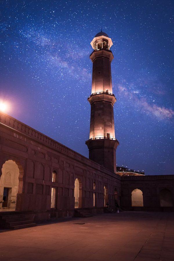 Illuminated minaret at Badshahi Mosque at night with the milky way seen behind it