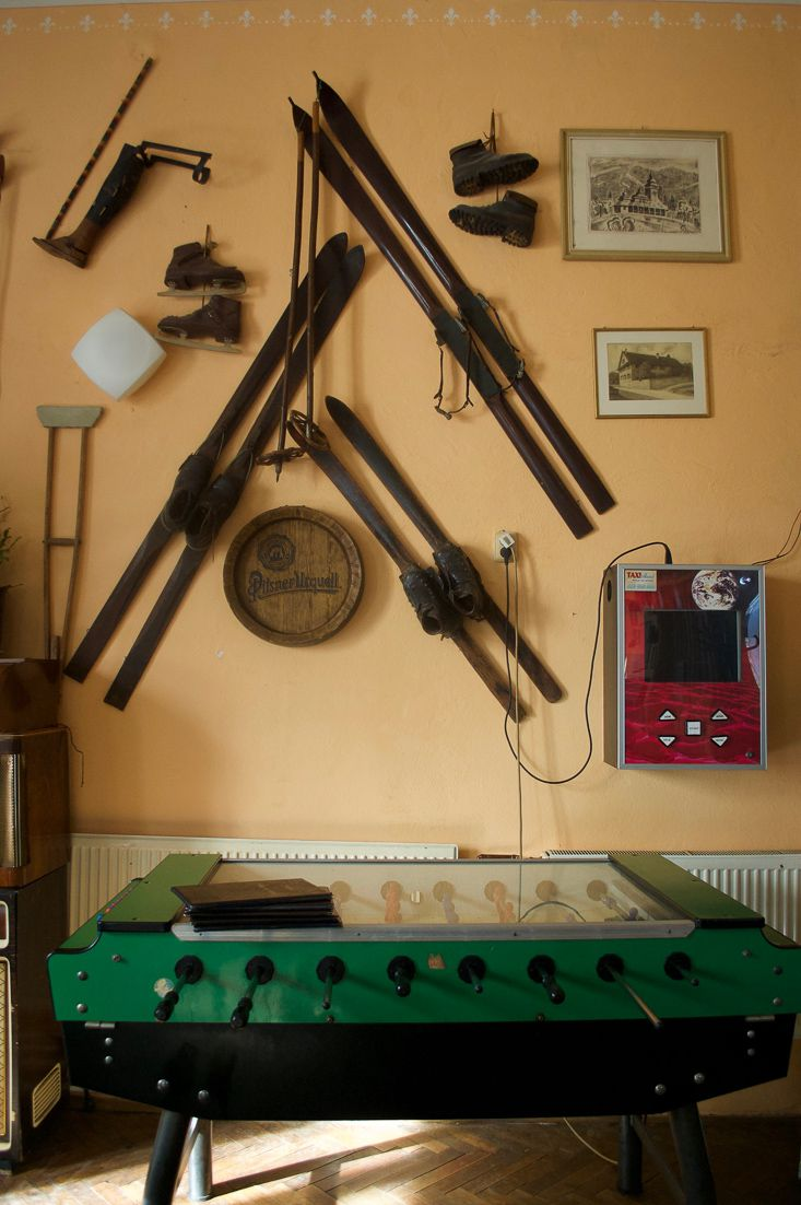 Photo inside a pub showing some vintage ski equipment that is hung on the wall as well as an old foosball table in front.