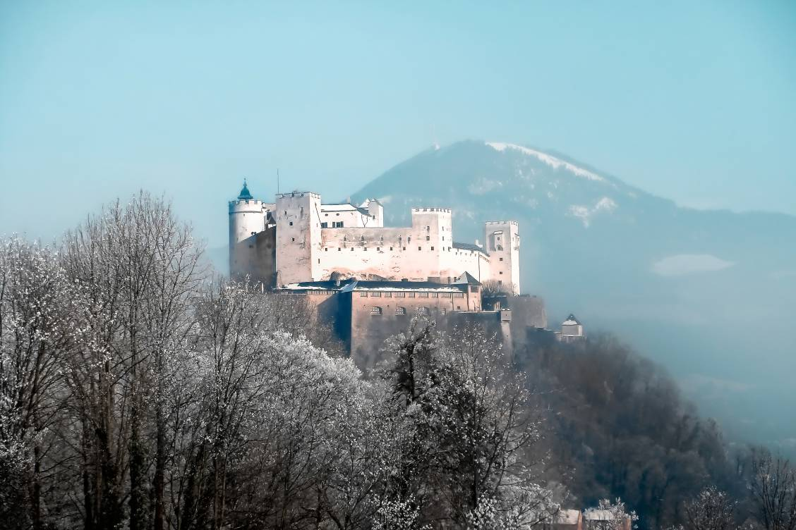 The stark white fortress, Festung Hohensalzburg in Austria with a single mountain behind it in the distance.