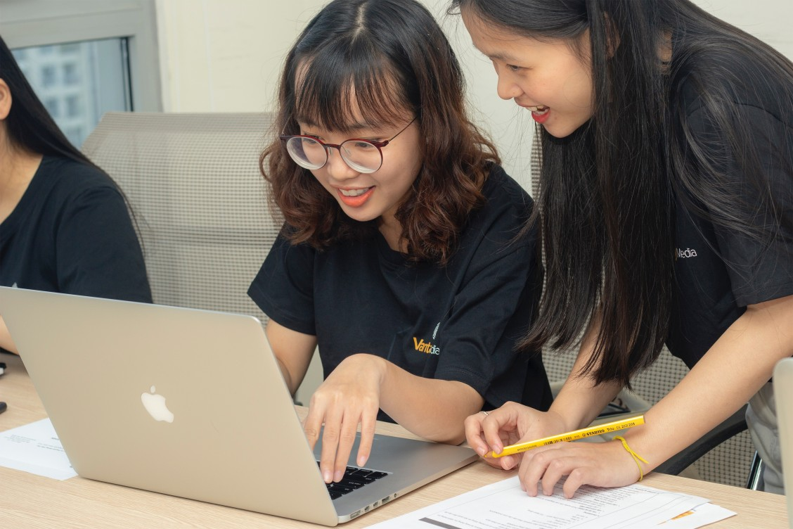 Two girls, one wearing glasses and one without, looking at a Macbook.