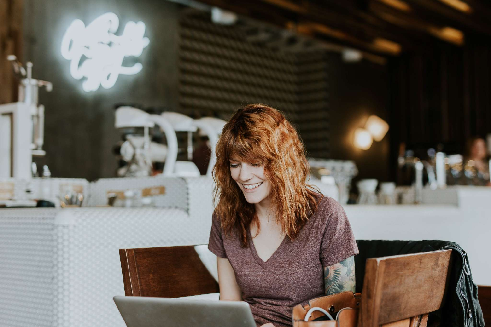 A tattooed woman sitting in a cafe and looking at laptop