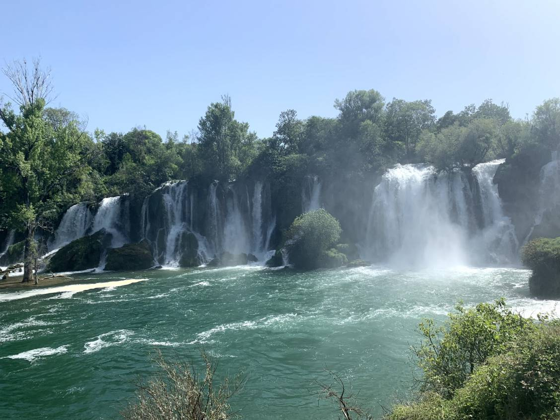 A view of Kravice Falls where you can see about 15 cascades lined up next to each other all emptying into one pool.