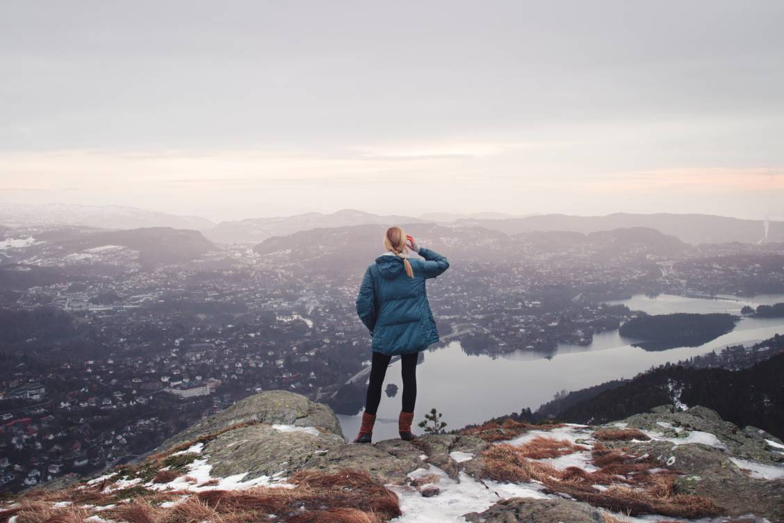 Photo of a blonde woman in a blue jacket looking out at a viewpoint atop Løvstakken in Bergen, Norway