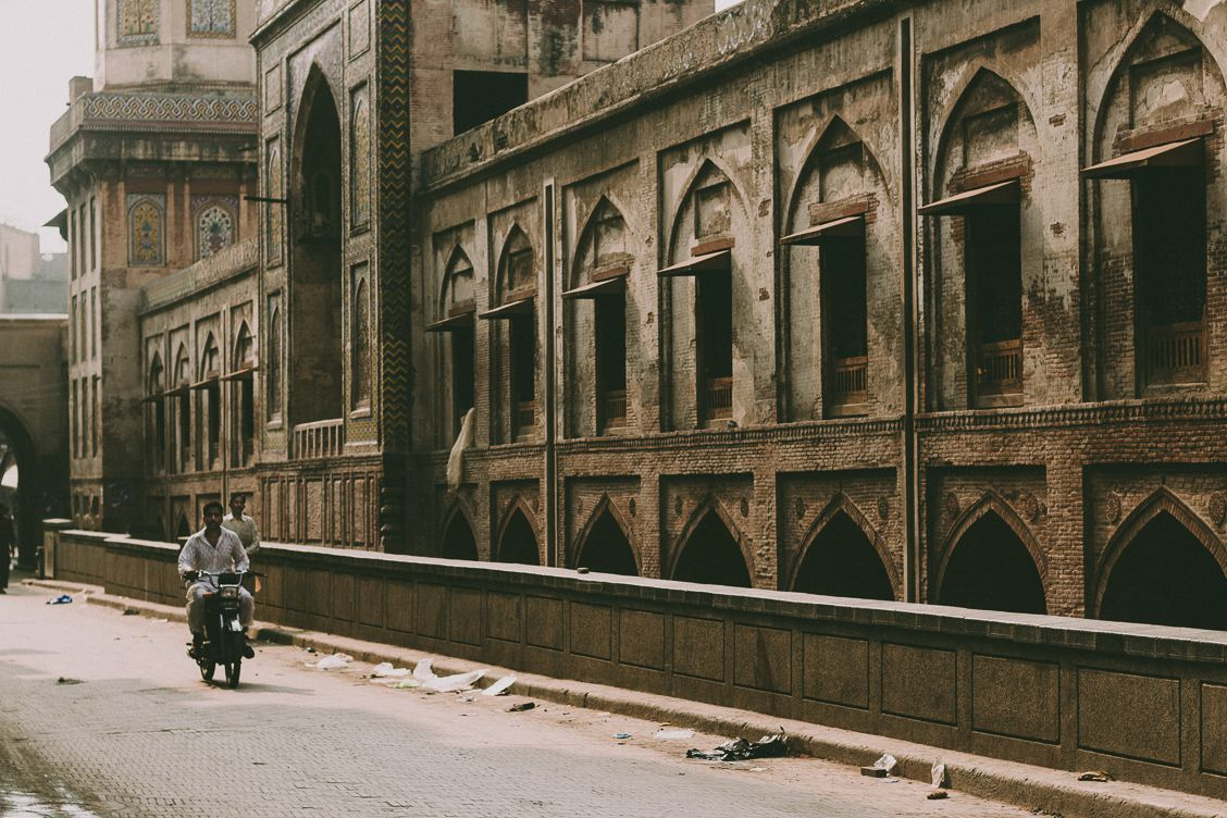 Man riding a motorbike next to an abandoned building in Lahore, Pakistan