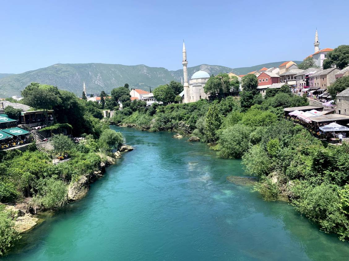 Photo taken from the old bridge in Mostar of the city sitting along the right side of the river