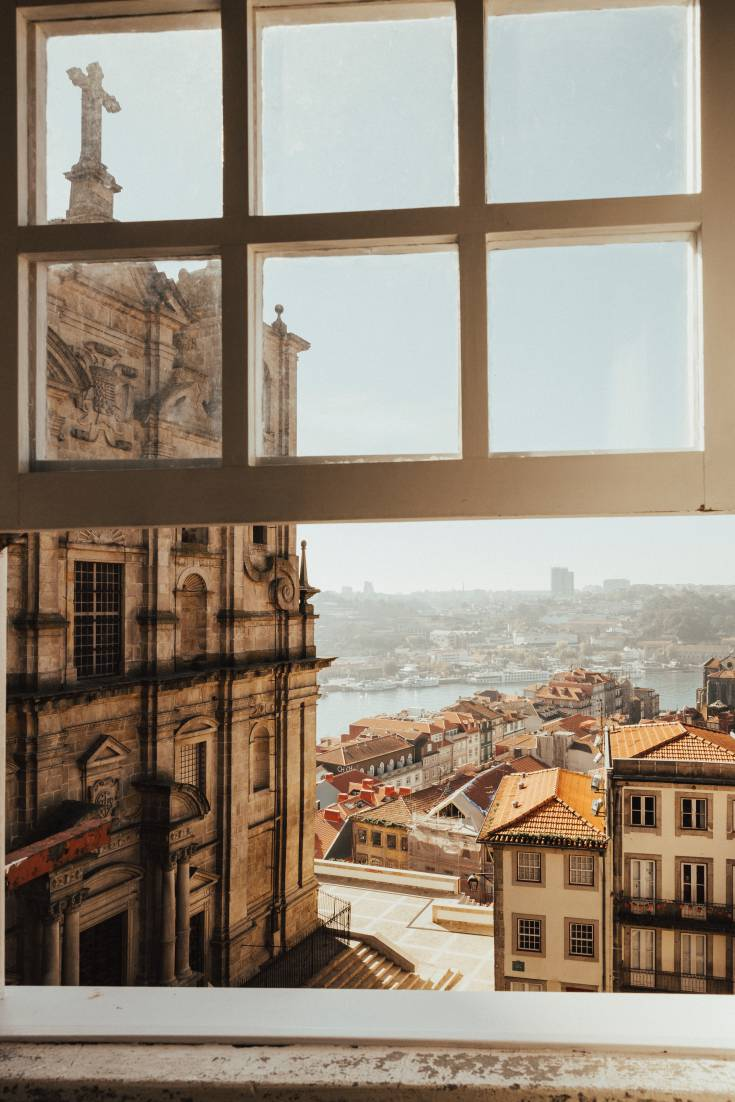 Photo taken from a window looking out the city of Portugal with an old cathedral in the foreground.