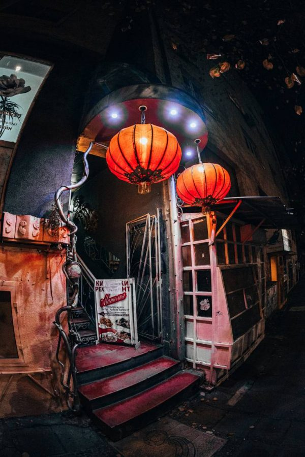 Photo of a modest restaurant entrance at night featuring two illuminated red lanterns in Sofia, Bulgaria.