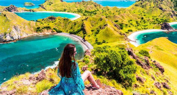 Solo female looking out across Komodo National Park in a beautiful blue dress which matches the colour of the sea