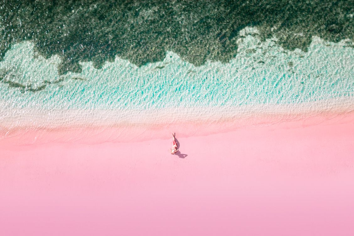 Aerial view of a solo female traveller lying down on the pink beach in Indonesia