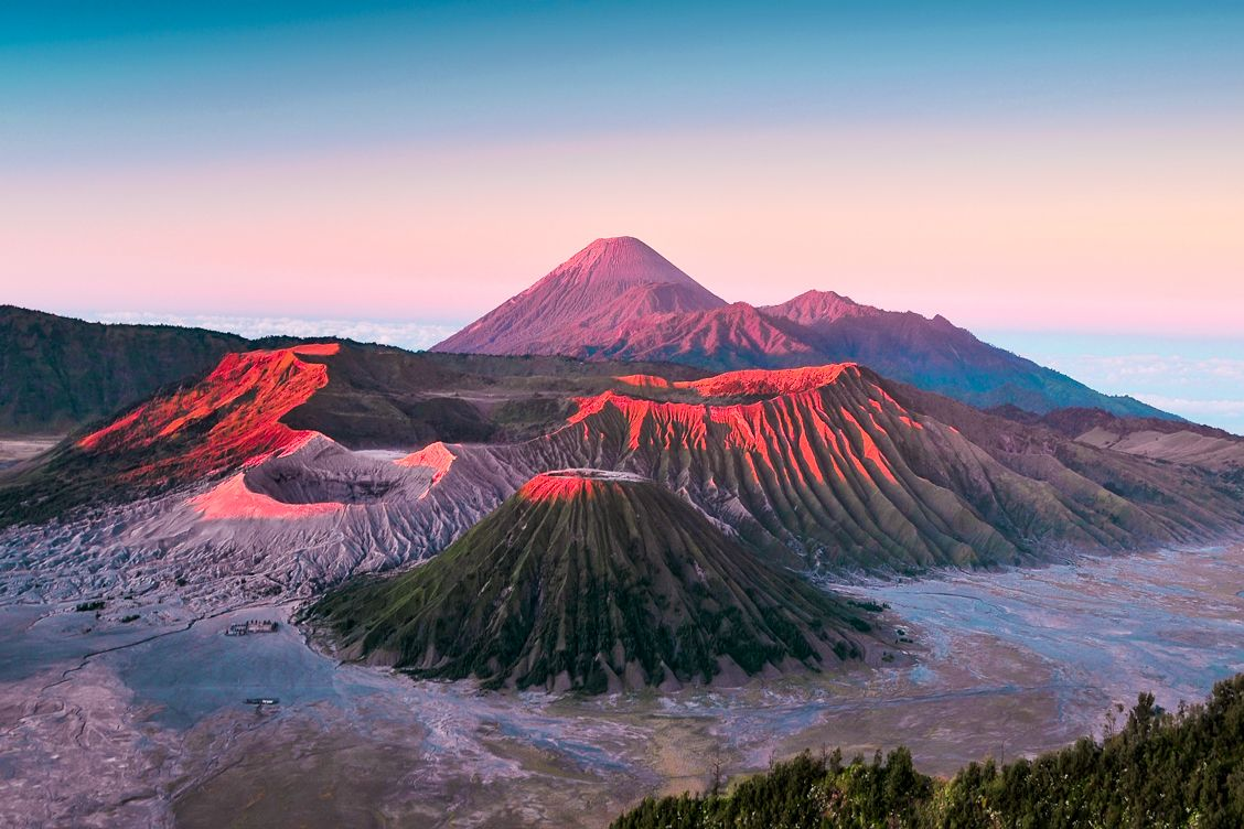 The spectacular Mount Bromo in Indonesia at sunrise covered in pinks, reds and orange colours from the sun