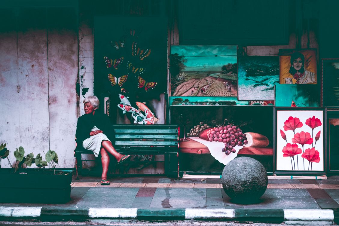 Local lady sitting on a bench chilling out in front of a shop on the streets of Bandung