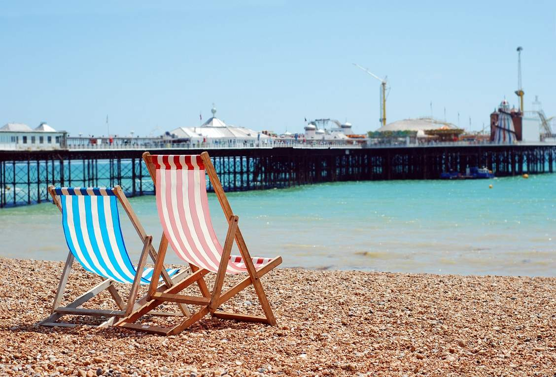 A red and blue deckchair on Brighton Beach looking out to Brighton Pier