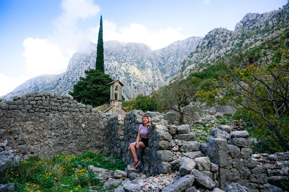 Photo of Alice resting at the ruins of St. John Church on the Ladder of Kotor