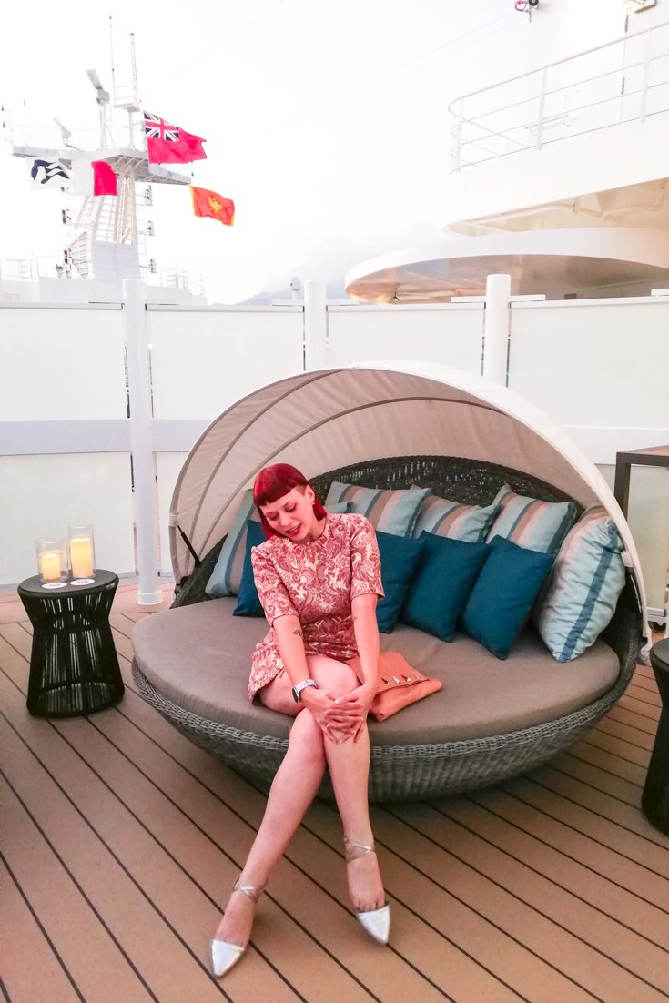 Photo of Alice sitting on a circular couch on the balcony of the Sky Suite