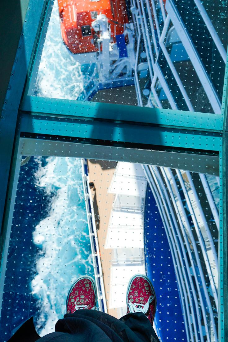 Photo of Alice standing on the glass floor of the seawalk looking down onto the side of the deck and the ocean.