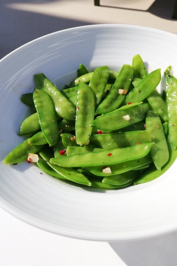 Photo of a white bowl filled with cooked edamame that have been garnished with some spices