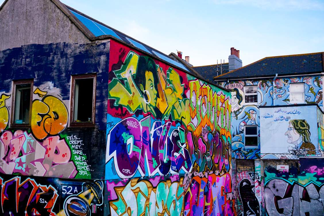 Graffiti and street art mix in vibrant colours on the back of houses in the backstreets of Brighton