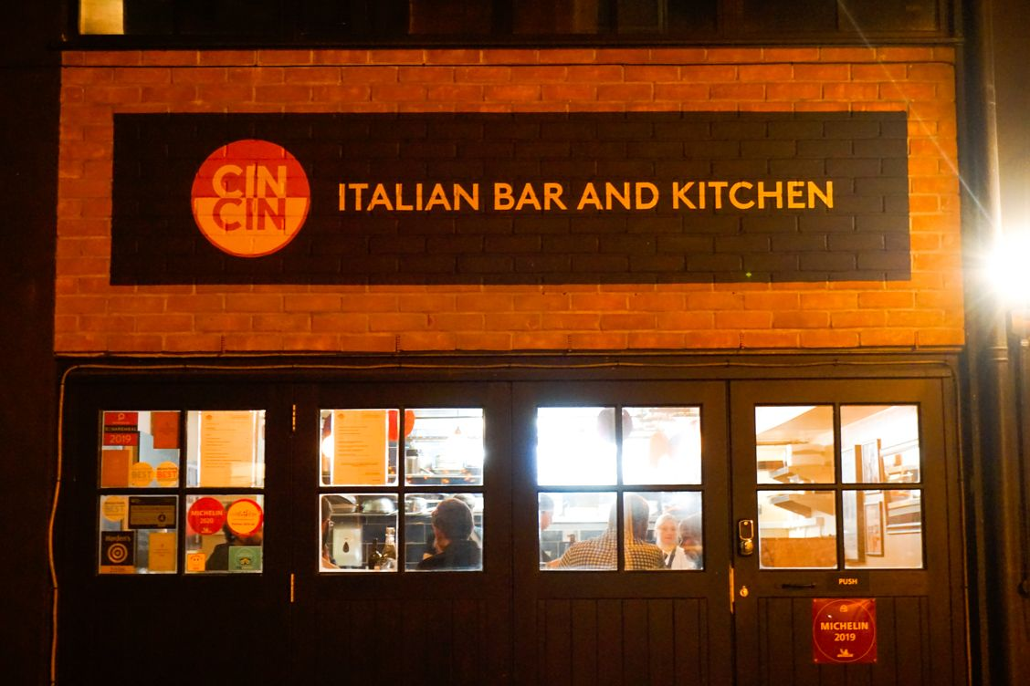 The outside of Cin Cin Restaurant in Brighton, with red brick walls and black garage doors