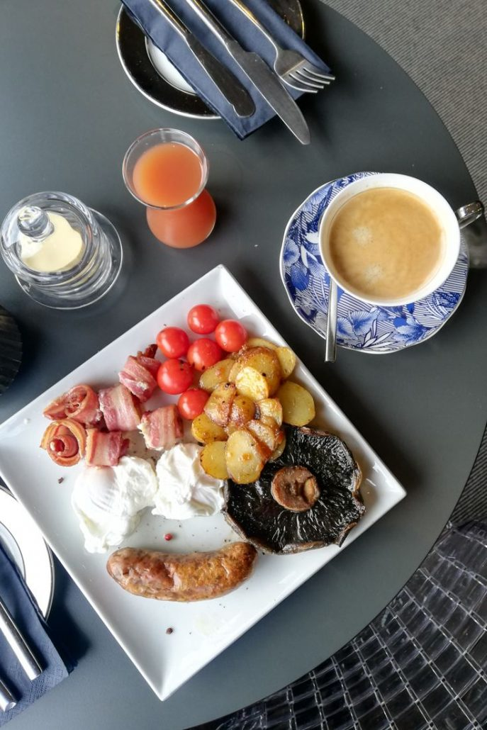 Full English cooked breakfast including tomatoes, mushrooms, potatoes, egg, bacon and sausage at The Square Hotel Brighton