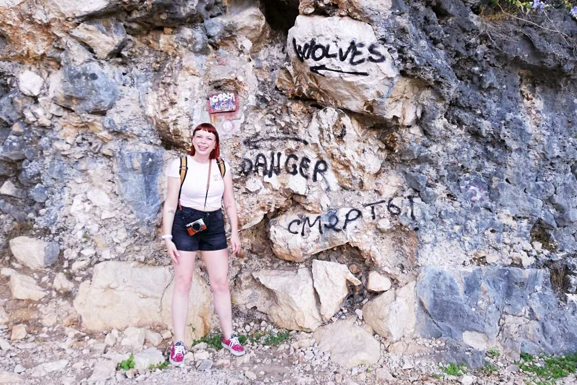 Photo of Alice in front of a rock face with graffiti warning about wolves in the area