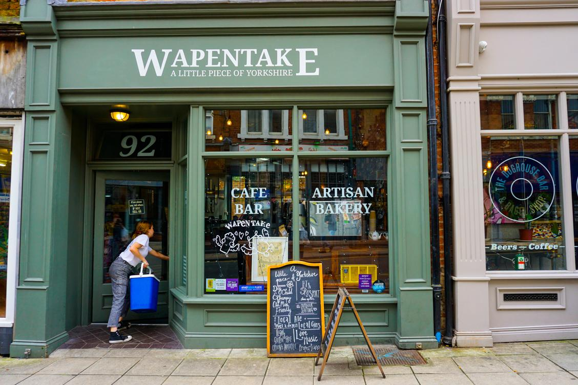 A lady walking into Wapentake pub and restaurant in Leeds Centre